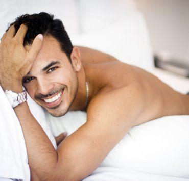 beautiful man laying on bed