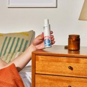 white man in bed reaching for lubricant bottle on wooden dresser