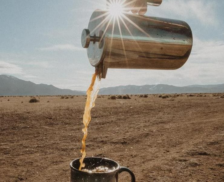 chrome coffee holder pouring coffee into a mug in the desert