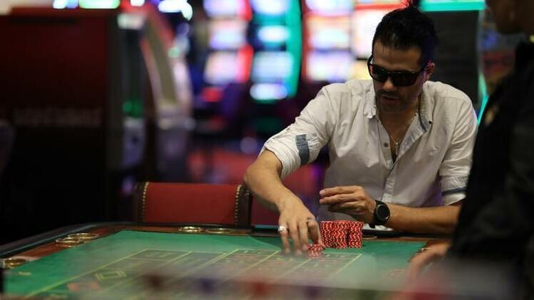 man gambling at poker table in white shirt